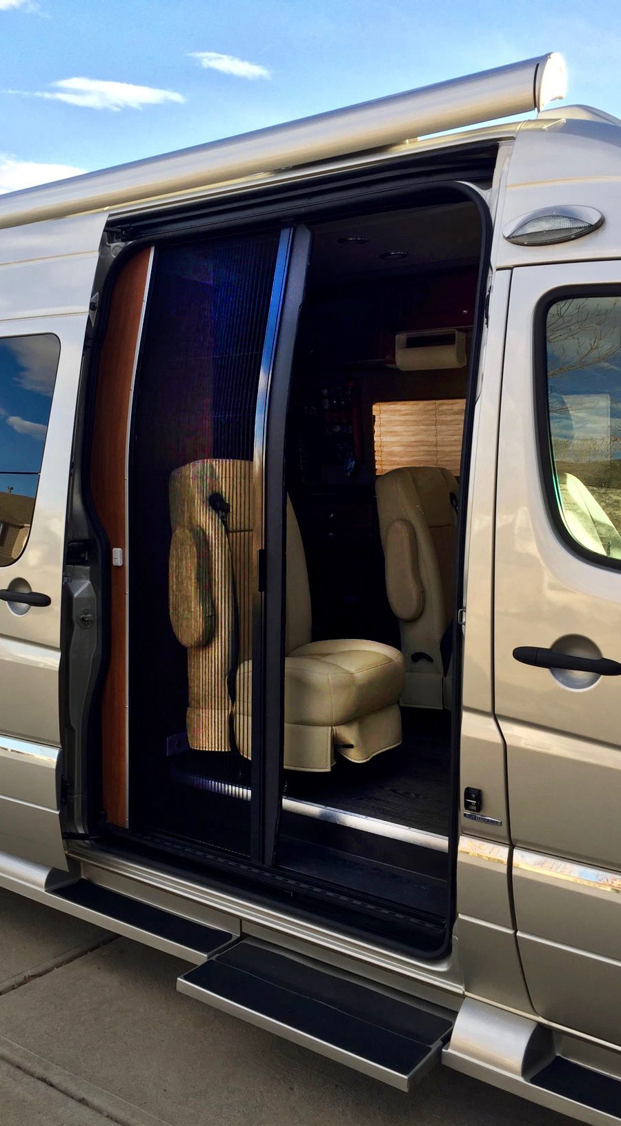 Retractable screen door shown half open on a RoadTrek conversion van.